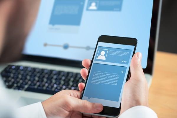 Businessman using smartphone against website interface