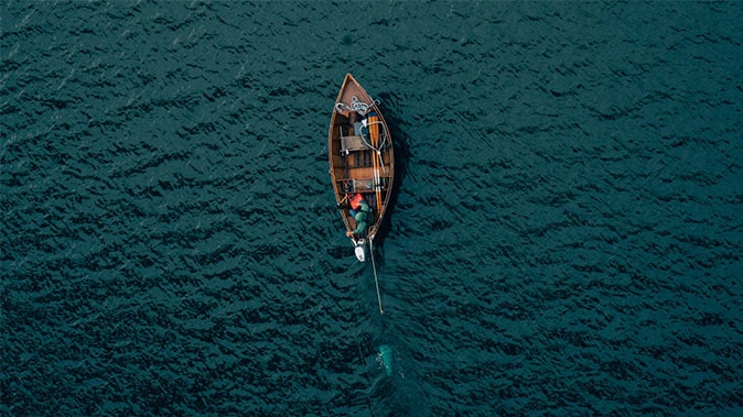 A Man In A Boat Surrounded By Deep Blue Water