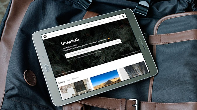 An IPad On A RuckSack Portraying The Unsplash Website