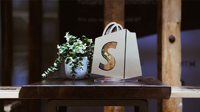 The Shopify Logo On A Table With A Plant